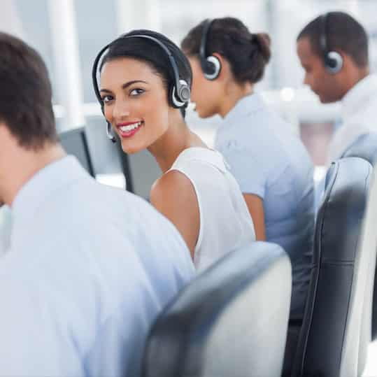 Call center employee working among her colleagues with headsets on.